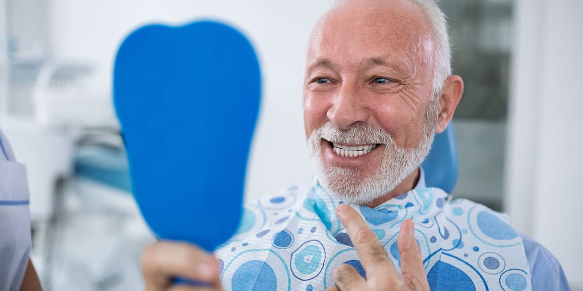 older man in dental chair holding mirror, smiling and pointing at teeth